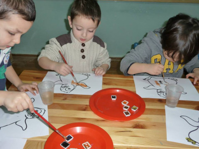 Here the children are using watercolor to paint dancing penguin coloring pages.